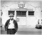 Man stands in front of Supreme Body Shop on Guadalupe Street, Santa Fe, New Mexico