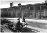 Couple sits outside Fuller Lodge, designed by John Gaw Meem and built in 1928, Los Alamos, New...