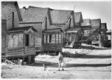 Woman, baby, and dog walk beside homes in Madrid, New Mexico