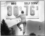 Man changes gas prices on sign during gas shortage, Santa Fe, New Mexico