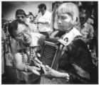 Ramona Tenorio reads plaque held by Delores Atencio, both of Santo Domingo Pueblo, at dedication...