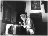 Woman lights candles at Santuario de Chimayo, New Mexico