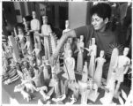 Sabinita Lopez Ortiz sets out wood carvings and santos at Spanish Market, Santa Fe, New Mexico