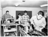 Students using wood working machinery while teacher supervises, New Mexico