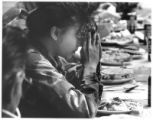 Carina Gonzales prays before a meal to honor the 720th National Guard Transportation Unit before...
