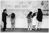 Children at Santa Fe Boys and Girls Club work on phase one of a 500-foot mural on West Alameda...