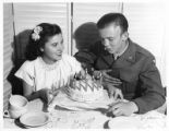 Woman presents a birthday cake to a GI, USO Club, Santa Fe, New Mexico