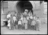 Group portrait of school children in front of public school, Cimarron, New Mexico