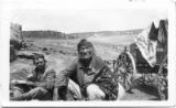Navajo man beside wagon, joins another man (Howard Raper?) during a snack stop