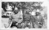 Three men sit next to one another on bench, Isleta Pueblo