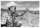 Bud Hagerman, member of the metropolitan water board, examines dry conditions