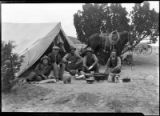 Men and horse by tent at ranch camp