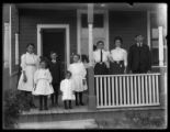 Unidentified children, women and man on porch