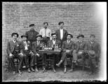 Men standing and sitting at table with bottles