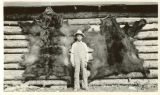 Unidentified boy poses in front of mounted bear skins