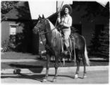 Unidentified woman on horse carries flag