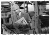 Robert McKinney, owner of the Santa Fe New Mexican, grabs a copy of the newspaper off the press