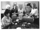 Las Jardineras Garden Club prepares packages for service members.  Left to right: Greta Goodrich,...