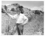 Frank Ortiz, ranger, with fence made of bed springs, La Cienega, New Mexico