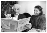 "Garth Williams, illustrator, with wife Leticia and Dilys, nine, looking at book ""Ride a..."