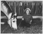 Girl with grazing horse at Cimarroncita Ranch Camp