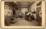 Studio photographer operating camera during portrait session, studio of Henry T. Hiester?...