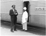 """Train stop in Albuquerque,"" African-American uniformed employee and cook in conversation"