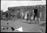 Unidentified group with hourse in front of adboe house, New Mexico