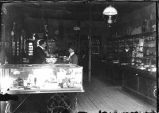 George Tambling Miller behind counter in his drug store, Hillsboro, New Mexico