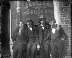 Group in front of Model Cash Grocery, man on right is Phil H. Doll, Las Vegas, New Mexico