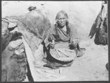 Hopi woman shelling corn