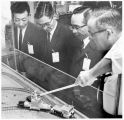 Tatsuo Kido and Ryuzo Veda from Japan view a model at the Los Alamos Scientific Laboratory, Los...
