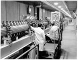 Technicians tune one of the sections of the side-coupled cavity stage of the Los Alamos Meson...