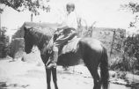 Olive Rush on horseback in the garden at 690 Canyon Road, Santa Fe, New Mexico