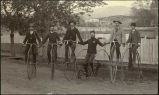 Bicyclists posed by picket fence. From left to right Stikey, Widmeyer, unidentified, Rev. E.L.H....