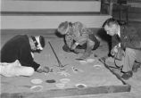 Navajo men working on the Dedication for War sandpainting, New Mexico
