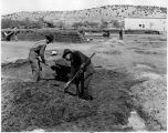Men mixing mud for adobe bricks, New Mexico