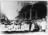 Large group of children waiting at the railroad depot to greet the William Randolph Hearst...