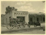 Wagon loaded with firewood in front of Palace of the Governors, Santa Fe, New Mexico
