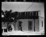 """A line of chili hanging from rack to dry on top of an adobe house at San Juan Indian Pueblo...."