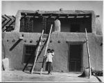 """San Juan Indian Pueblo, mother and  baby in front of their home. October 1940"""