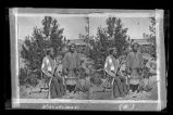 """Navajo Indian and woman in full costume with rifle"""