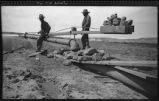 Workers using high pressure water at Black Rock Dam near Zuni, New Mexico
