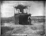 Man standing next to structure in the fields, San Ildefonso Pueblo, New Mexico