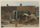 Family plastering adobe home, New Mexico