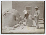 Woman using horno oven, Chamita, New Mexico