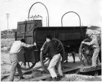 Men unloading wagon off truck, New Mexico