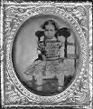 Untitled (young girl in green plaid dress sitting on chair)