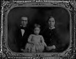 Untitled (1/2 length seated man and woman with child between them, child is out of focus)