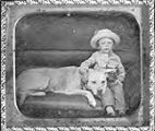 Untitled (boy in brimmed hat seated with dog on couch)